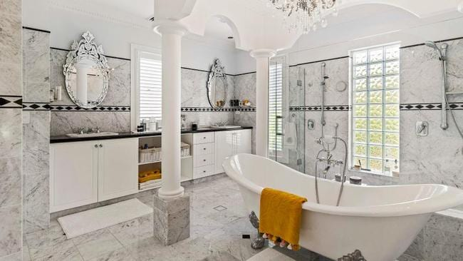 One bathroom is all marble, with a chandelier and claw foot bath.