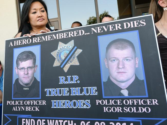 Memorial ... A sign with images of officers Alyn Beck and Igor Soldo is displayed during a vigil outside CiCi's Pizza in Las Vegas, Nevada.