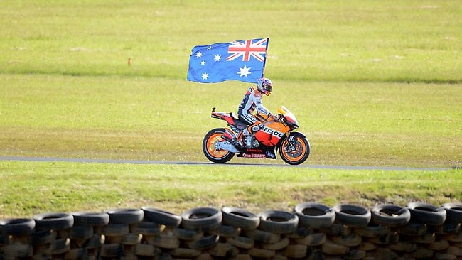 Casey Stoner hoists the Australian flag after his win. Picture: Wayne Ludbey