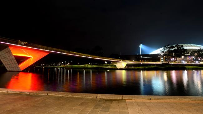 The Torrens River footbridge is lit up in the Crows colours. Picture: Sam Wundke