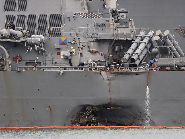 The damaged port aft hull of the USS John S. McCain is visible while docked at Singapore's Changi naval base in Singapore. The US Navy said in a statement yesterday that the Navy has relieved of duties its commander and executive officer. Picture: AP /Wong Maye-E