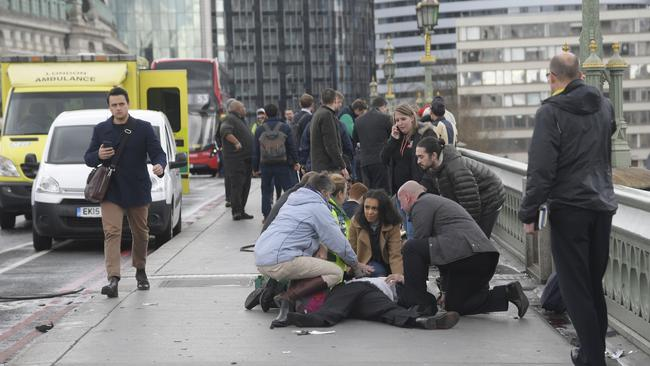 Injured people are assisted after a car mowed down pedestrians on London's Westminster Bridge. Picture: Reuters