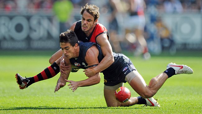 Bomber Sam Lonergan drives Blues defender Andrew Carrazzo into the MCG turf. Picture: Michael Dodge