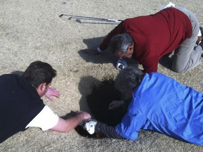 Hank Martinez,Ed Magaletta and Russ Nobbe, look into the sinkhole that swallowed fellow golfer Mark Minhal at the Annbriar Golf Course in Waterloo, Ill. Mihal was hoisted to safety with a rope and suffered a dislocated shoulder. AP/Courtesy of golfmanna.com, Mike Peters)