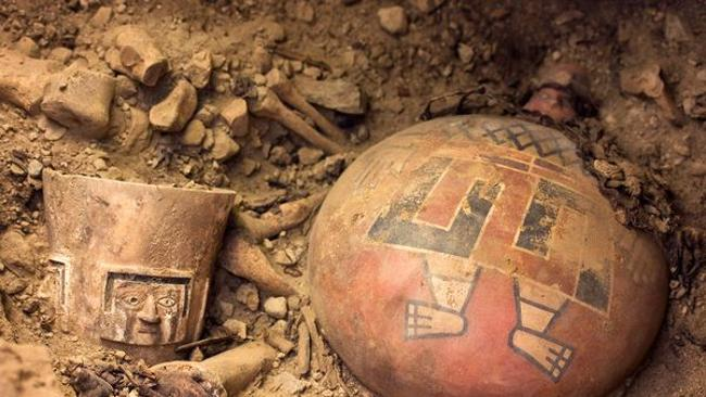 As archaeologists dug in one side chamber, they unearthed the remains of a Wari queen and several regal offerings, including a brilliantly painted ceramic flask (right) and an alabaster drinking cup (left). Picture: Patrycja Przadka Giersz / National Geographic