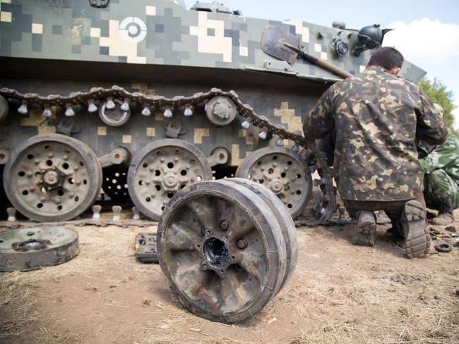 Hard grind ... Ukrainian servicemen repair a part of their armoured vehicle inside a military camp in the Donetsk region. Source: AFP
