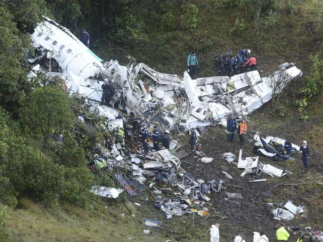 Rescue workers carry a body away from he wreckage of a chartered airplane that crashed in La Unio.