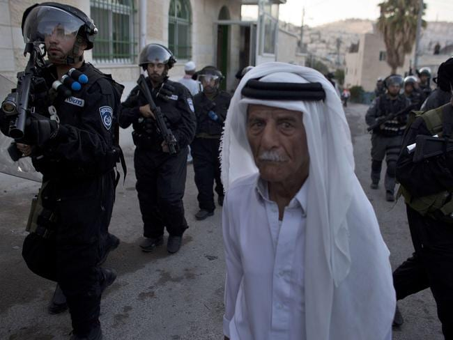 A Palestinian man walks past Israeli police officers. AFP PHOTO / AHMAD GHARABLI