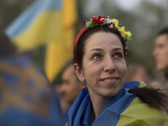 A brighter day? ... A woman wearing flowers on her head smiles during a rally in support of a united Ukraine in Donetsk, Ukraine.