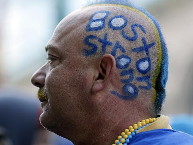 """Mike Poitras wears the slogan """"Boston Strong"""" on his head near the finish line of the 118th Boston Marathon. Picture: Charles Krupa"""