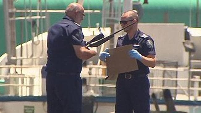 Police recover a rifle from the water, after the car plunged over the wharf. Picture: Cha