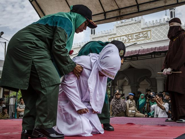 An acehnese woman is escorted off stage by sharia police women after receiving the cane in public from an executor known as 'algojo'. She was caned for spending time with a man who is not her husband. Picture: Ulet Ifansasti