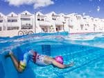 """© Petra Van Borm, Belgium, Entry, Open, Split Second, 2016 Sony World Photography Awards """"A young boy training hard in the pool to participate in the yearly triatlon while other kids are playing. The image is taken at Sandsbeach resort pool in Lanzarote."""""""
