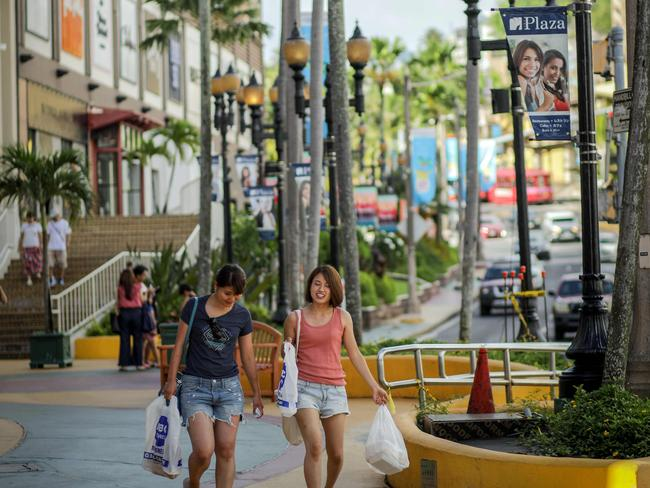 Tourists walk along a shopping area in the city of Tamuning on the island of Guam on August 10 after Pyongyang released a detailed plan to launch missiles towards the island. Picture: Robert Tenorio/AFP