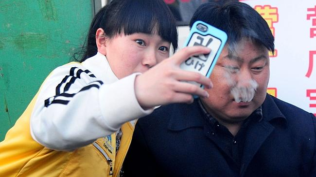 Star power... The unnamed lookalike poses for a fan's selfie at his barbecue stall in She