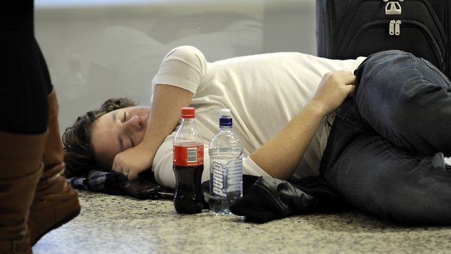 Steve Wood tries to get some sleep while waiting for his flight at Melbourne Airport. Picture: Jon Hargest
