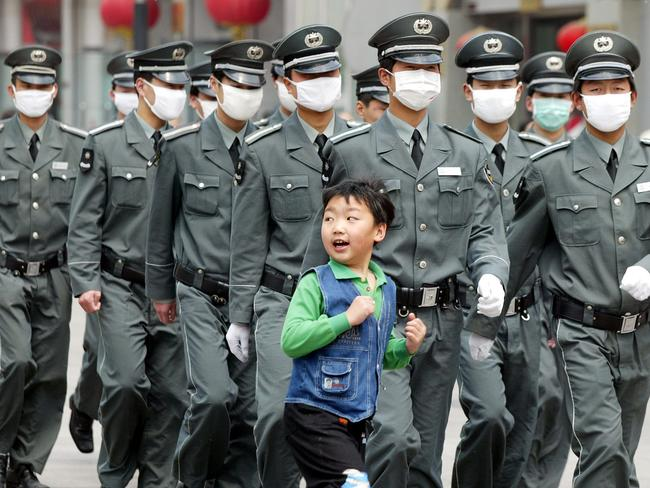 A young boy runs in front of a group of security guards wearing surgical masks to protect against the SARS virus as they patrol in Beijing, 2003. Picture: AP