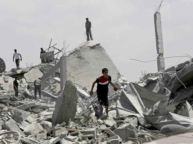 War ... Palestinians search through rubble of their destroyed houses hit by Israeli strikes in Khuzaa, in the northern Gaza strip. Picture: AFP