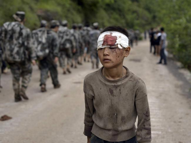 Hundreds dead...An injured child walks past rescuers heading towards the epicenter of the earthquake that struck the town of Longtoushan in Ludian county in southwest China's Yunnan province. Picture: AP