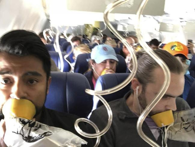 Marty Martinez left, appears with other passengers after a jet engine blew out on the Southwest Airlines Boeing 737 plane he was flying in. Picture: AP