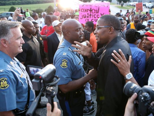 Stand off ... Col. Ron Replogle, left, and Capt. Ron Johnson talk with Malik Shabazz, president of the Black Lawyers for Justice (centre) during a march with protesters along W. Florissant Avenue in Ferguson Missouri on Saturday. Picture: AP Photo/St. Louis Post-Dispatch, David Carson