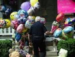 Cleveland's House of Horrors: a policeman carries balloons brought by well-wishers as Amanda Berry is about to arrive at her sister's house in Cleveland, ohio. . Three brothers have been arrested in connection with the kidnapping of three women. Photo: AFP/Emmanuel Dunand