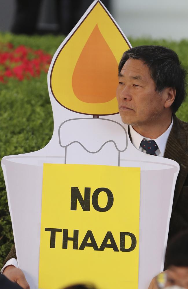A man holds a candle-shaped banner during a rally to oppose a plan to deploy an advanced US missile defence system in Seoul, South Korea. Picture: AP Photo/Lee Jin-man