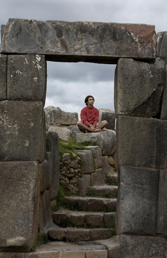A young man meditates in ancient Incan ruins outside Cuzco, Peru