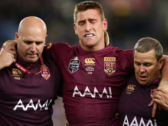 Brent Tate of the Queensland Maroons is helped off the field after an injury during game two of the State of Origin series against NSW.