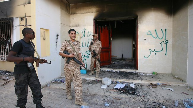 Libyan military guards check one of the burnt out buildings at the US consulate in Benghazi after the terrorist attack in September last year.