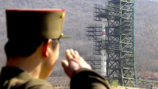 A North Korean soldier salutes the missile on its launch platform / AP
