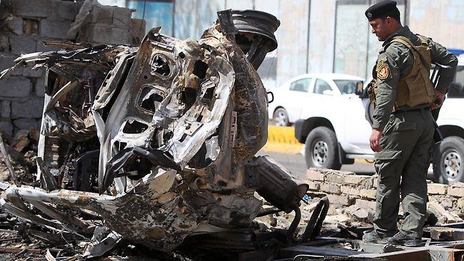 A member of Iraq's internal security forces inspects the damage outside the Iraqi justice ministry in Baghdad on March 15, 2013.