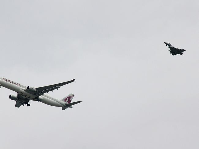 Bomb threat...A military fighter jet escorts a passenger jet as it comes in to land at Manchester airport. Picture: Getty
