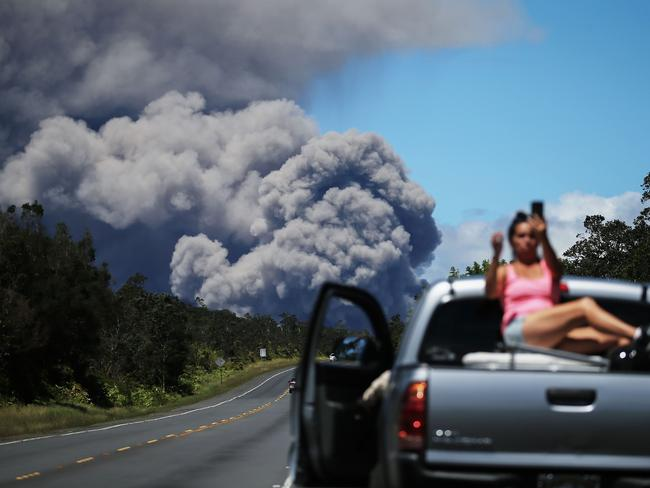 Evacuation is advised, but first, a selfie. Picture: AFP