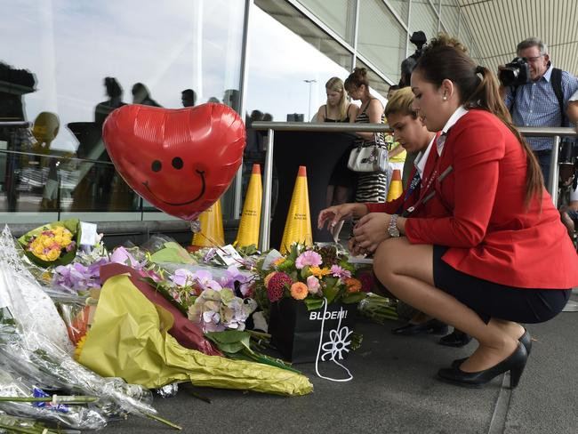 Respects ... flight attendants place flowers in front of Schiphol airport, two days after Malaysia Airlines flight MH17 crashed in eastern Ukraine. Picture: John Thys