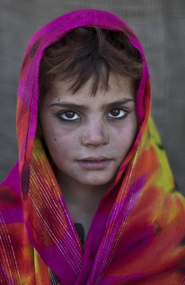 Afghan refugee girl, Nazmina Bibi, 7, poses for a picture, while playing with other children in a slum on the outskirts of Is...