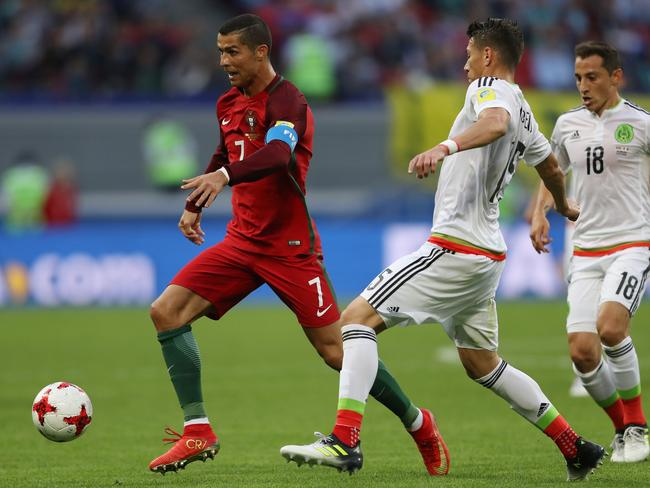 Cristiano Ronaldo of Portugal attempts to take the ball past Hector Moreno of Mexico.