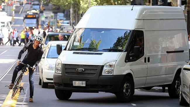 A van and a cyclist nearly collide on Collins St.