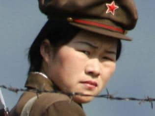 03/06/2009. In this photo taken on June 3, 2009, a female North Korean soldier looks out from behind a barded wire fence around a camp on the North Korean river banks across from Hekou, northeastern China's Liaoning province. (AP Photo/Ng Han Guan)