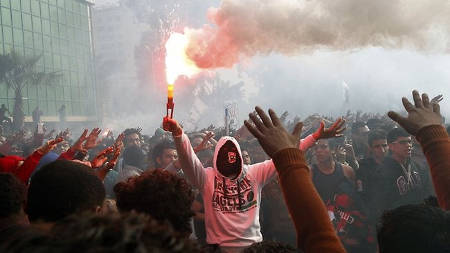 An Egyptian fan of Al-Ahly football club lights a flare as club supporters celebrate outside its headquarters in Cairo on January 26, 2013 after a court sentenced 21 people to death over a football riot that killed more than 70 people last year. The clashes in Port Said in February last year between fans of home side Al-Masry and Cairo's Al-Ahly had left more than 70 people dead and sparked days of violent protests in Cairo, in which another 16 people were killed. AFP PHOTO / MOHAMMED ABED
