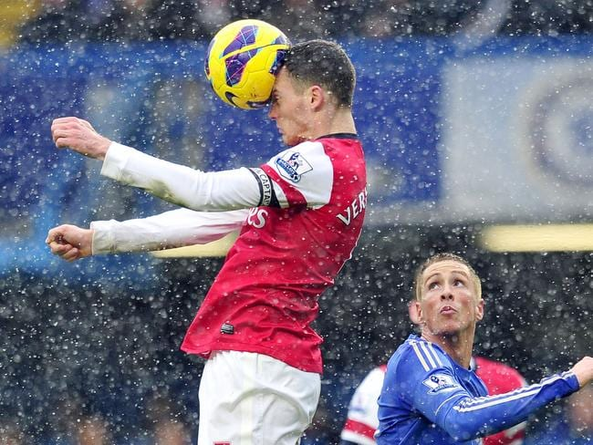Arsenal's Belgian defender Thomas Vermaelen (L) heads the ball as Chelsea's Spanish striker Fernando Torres (R) watches.
