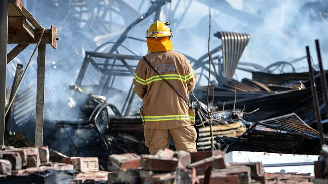 A firefighter examines the remains of the building. Picture: Ellen Smith