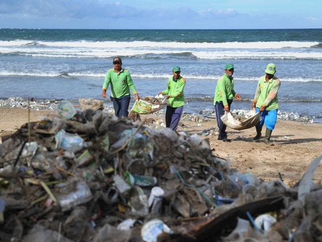This photo taken on December 19, 2017 shows rubbish collectors clearing trash on Kuta beach near Denpasar, on Indonesia's tourist island of Bali. The palm-fringed shoreline of Bali's Kuta beach has long been a favourite with tourists seeking sun and surf, but nowadays its golden shores are being lost under a mountain of garbage. / AFP PHOTO / SONNY TUMBELAKA / TO GO WITH Indonesia-rubbish-Bali-environment,FEATURE by Bagus Saragih