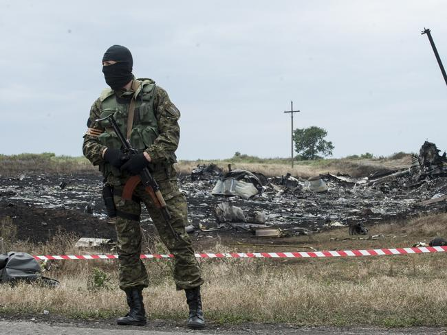 Crime scene ... A pro-Russian fighter guards the crash site of a Malaysia Airlines. Picture: AP
