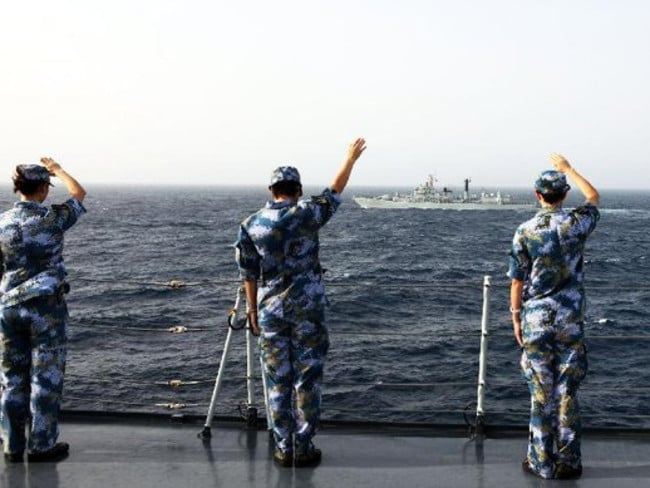 Chinese marines salute a passing warship while on exercise. Photo: Xinhua