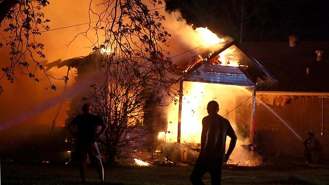 A person looks on as emergency workers fight a house fire caused by the explosion. Picture: AP