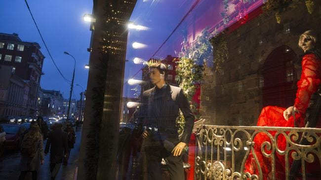 People walk past a shop window of the Central Department Store, decorated for Christmas, in Moscow, 16 December 2014. Picture: Pavel Golovkin
