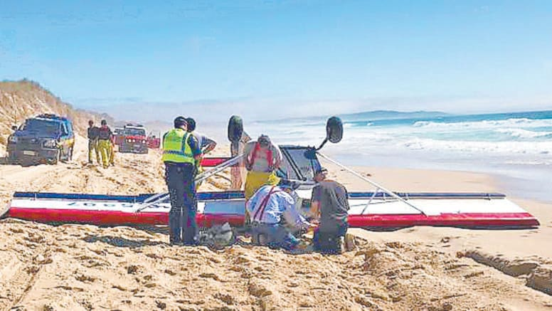 The light plane lies on its roof on the beach just north of St Helens. Pictures: TASMANIA FIRE SERVICE