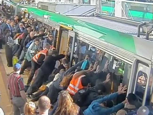 Train commuters work to free a man who became stuck in between the train and platform at Stirling station this morning. Picture: Public Transport Authority