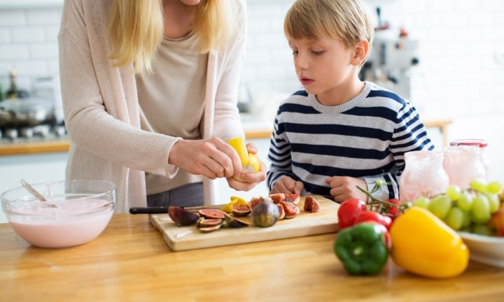 Portrait of mother and son in kitchen preparing food